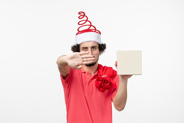 Vue de face du jeune homme avec cadeau de vacances sur mur blanc