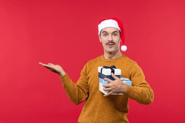 Vue de face du jeune homme avec des cadeaux sur un mur rouge clair