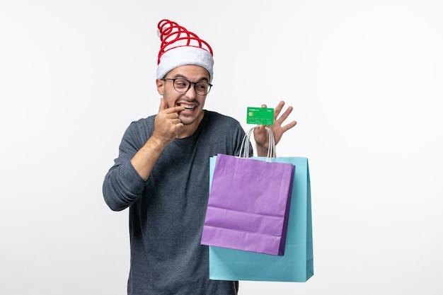 Vue de face du jeune homme avec carte bancaire et colis sur mur blanc