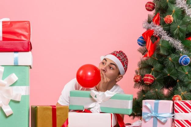 Vue de face du jeune homme célébrant noël autour de cadeaux sur mur rose