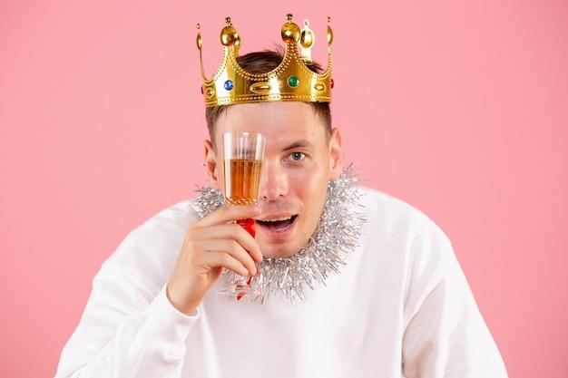 Vue de face du jeune homme célébrant noël avec boisson sur un mur rose clair