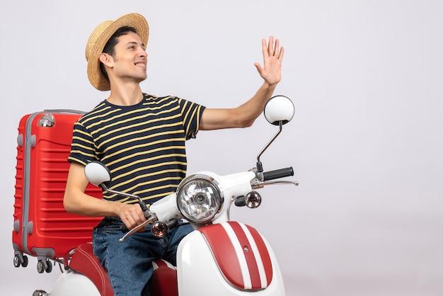 Vue de face du jeune homme avec un chapeau de paille sur un cyclomoteur hélant quelqu'un