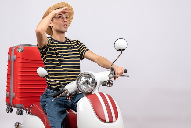 Vue de face du jeune homme avec chapeau de paille sur un cyclomoteur regardant quelque chose