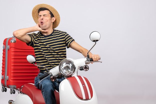 Vue de face du jeune homme avec un chapeau de paille sur un cyclomoteur tenant la gorge avec douleur