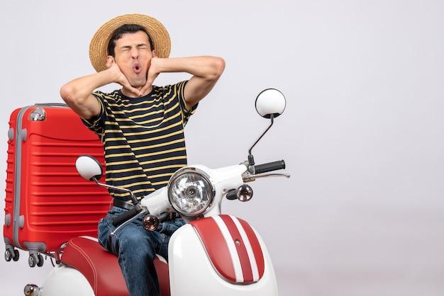 Vue de face du jeune homme avec un chapeau de paille sur un cyclomoteur tenant sa gorge avec douleur