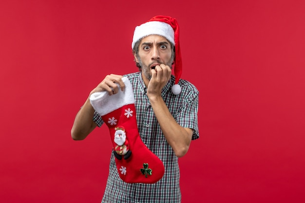 Vue de face du jeune homme avec chaussette de noël sur le mur rouge