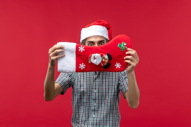 Vue de face du jeune homme avec chaussette de noël rouge sur mur rouge