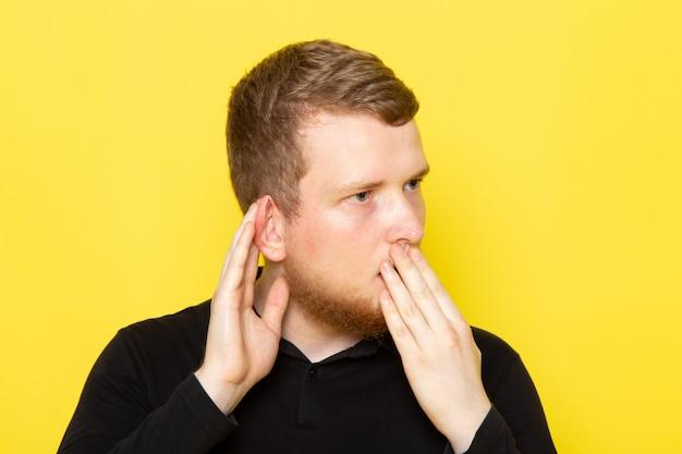 Vue de face du jeune homme en chemise noire posant et essayant de cœur avec le choc
