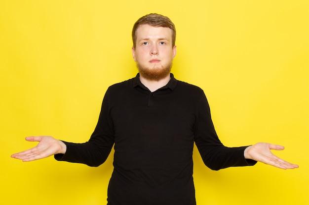 Vue de face du jeune homme en chemise noire posant avec une expression confuse