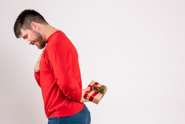 Vue de face du jeune homme en chemise rouge cachant le cadeau de noël derrière son dos sur un mur blanc
