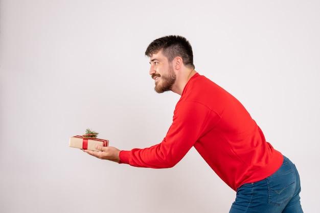 Vue de face du jeune homme en chemise rouge donnant un cadeau de noël sur un mur blanc