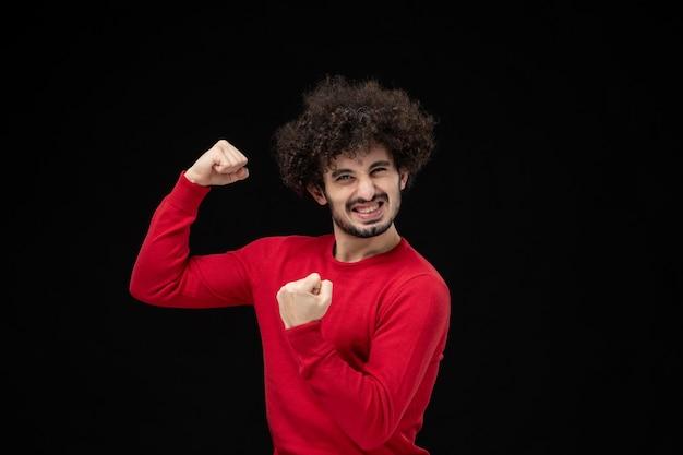 Vue de face du jeune homme en chemise rouge fléchissant sur le mur noir