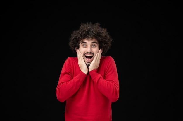 Vue de face du jeune homme en chemise rouge sur mur noir