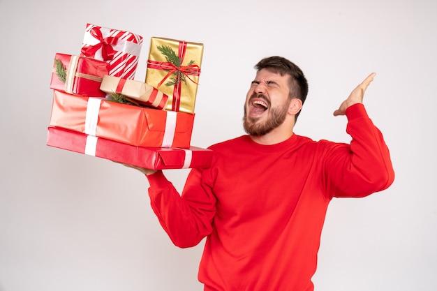 Vue de face du jeune homme en chemise rouge tenant des cadeaux de noël sur un mur blanc
