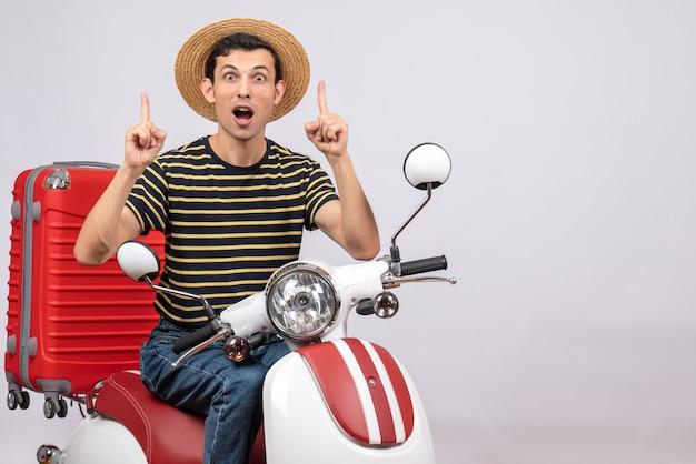 Vue de face du jeune homme choqué avec un chapeau de paille sur un cyclomoteur pointant au plafond