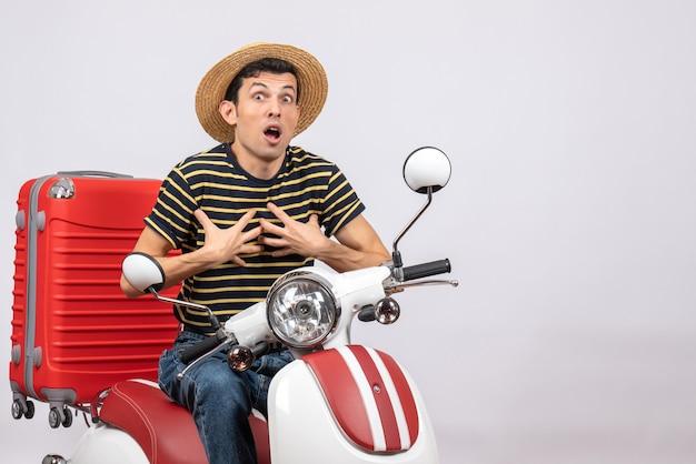 Vue de face du jeune homme choqué avec un chapeau de paille sur un cyclomoteur