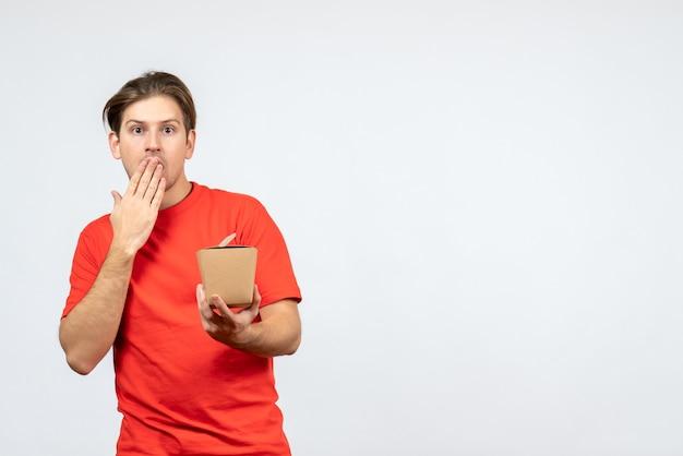Vue de face du jeune homme choqué en chemisier rouge tenant une petite boîte sur fond blanc