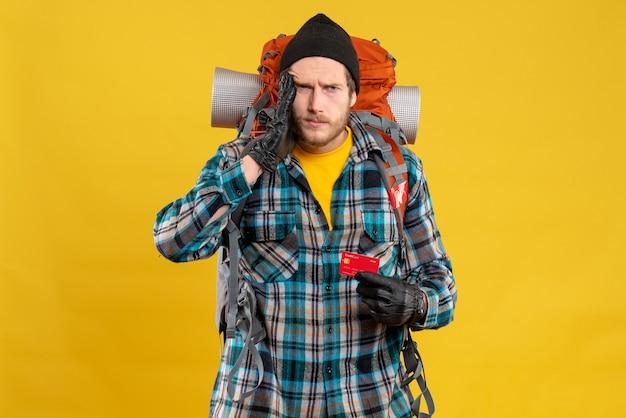 Vue de face du jeune homme confus avec backpacker holding carte bancaire
