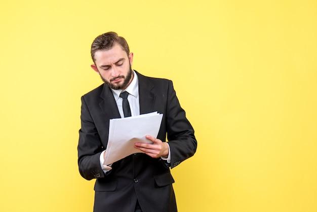 Vue de face du jeune homme en costume noir note avec un document vierge de stylo sur le mur jaune