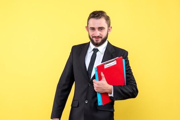 Vue de face du jeune homme en costume noir tenant le presse-papiers rouge et dossier bleu souriant sur jaune