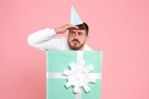 Vue de face du jeune homme debout à l'intérieur de la boîte présente sur un mur rose clair