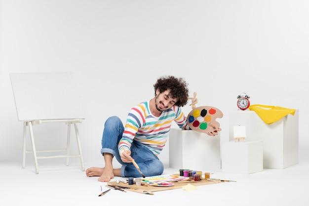 Vue de face du jeune homme dessinant des peintures sur un mur blanc