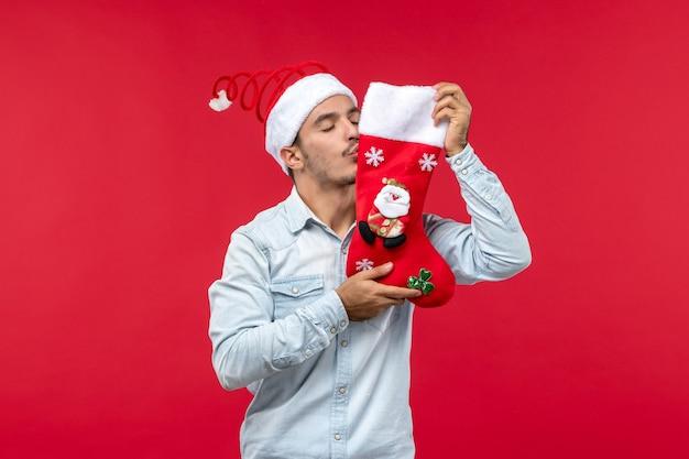 Vue de face du jeune homme embrassant la chaussette de noël sur le mur rouge