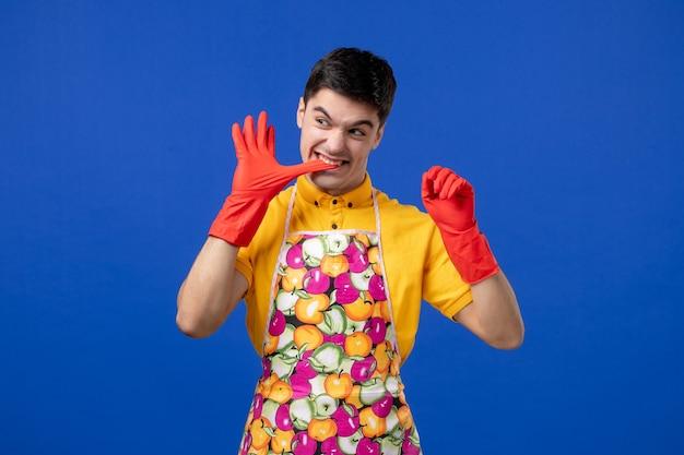 Vue de face du jeune homme enlevant ses gants sur le mur bleu