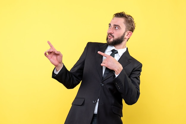 Vue de face du jeune homme étonné homme d'affaires pointant du doigt de côté sur jaune