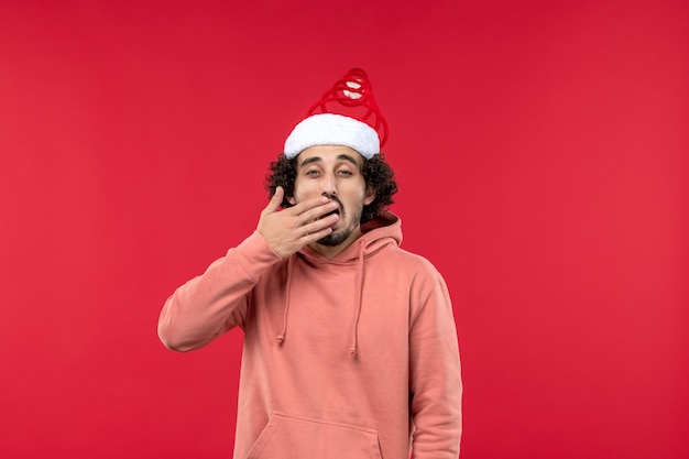 Vue de face du jeune homme avec une expression de bâillement sur le mur rouge