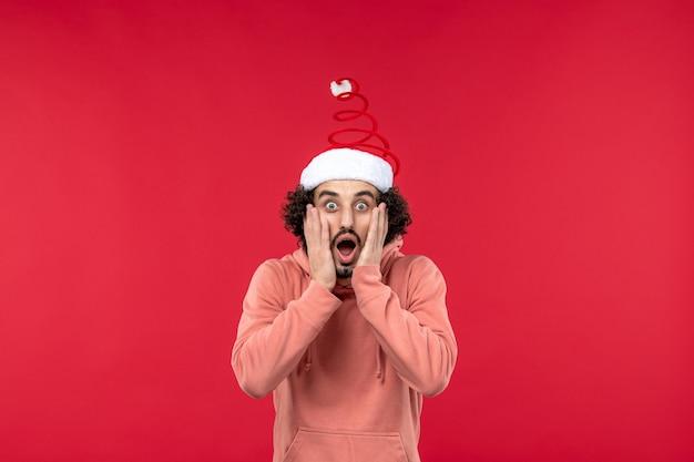 Vue de face du jeune homme avec une expression choquée sur le mur rouge