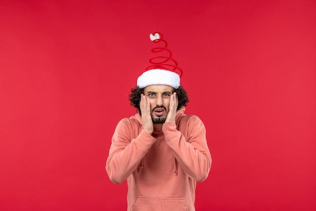 Vue de face du jeune homme avec expression confuse sur mur rouge