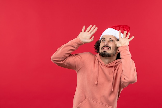 Vue de face du jeune homme avec une expression effrayée sur le mur rouge