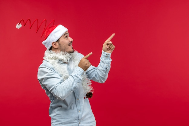 Vue de face du jeune homme avec une expression excitée sur le mur rouge