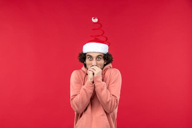 Vue de face du jeune homme avec une expression frissonnante sur le mur rouge