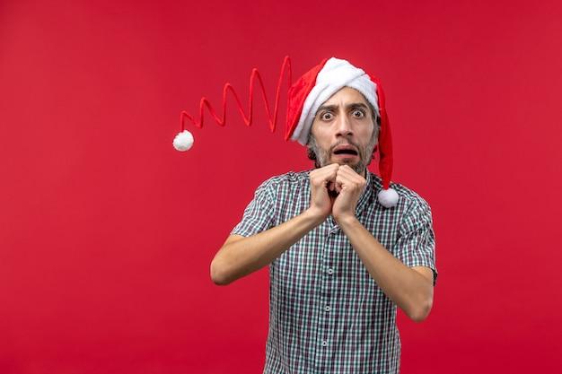 Vue de face du jeune homme avec une expression nerveuse sur le mur rouge