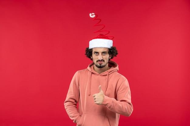 Vue de face du jeune homme avec une expression sérieuse sur le mur rouge