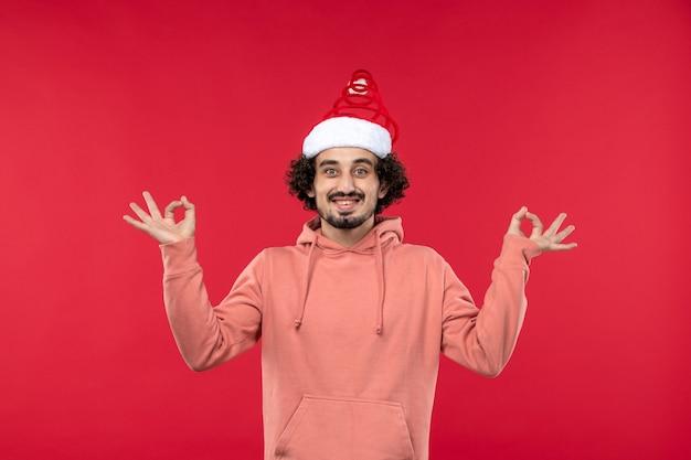 Vue de face du jeune homme avec une expression souriante sur un mur rouge clair