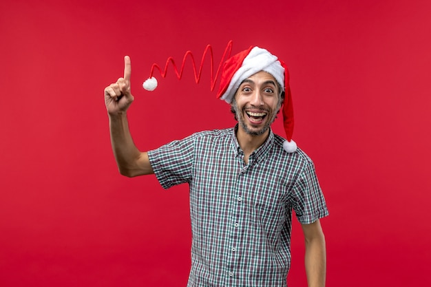 Vue de face du jeune homme avec une expression souriante sur le mur rouge