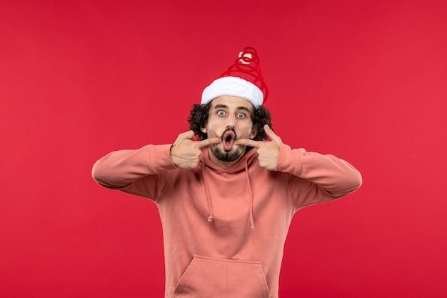 Vue de face du jeune homme avec une expression surprise sur le mur rouge