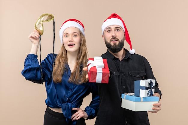 Vue de face du jeune homme avec femme tenant des cadeaux sur le mur rose