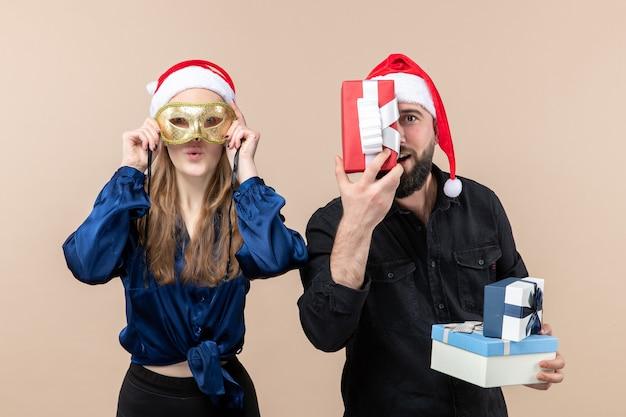 Vue de face du jeune homme avec femme tenant des cadeaux et portant un masque sur un mur rose