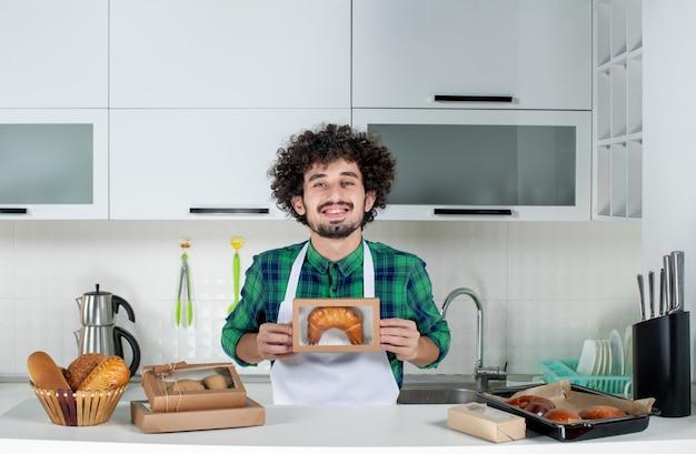 Vue de face du jeune homme fier tenant une pâtisserie fraîchement cuite dans une petite boîte dans la cuisine blanche