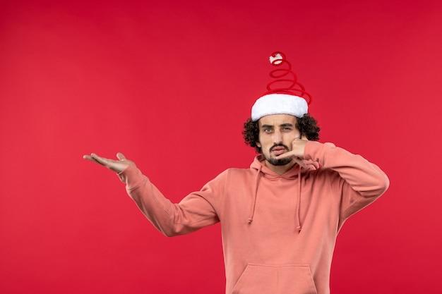 Vue de face du jeune homme imitant l'appel téléphonique sur un mur rouge clair