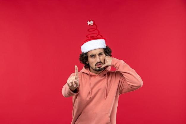 Vue de face du jeune homme imitant l'appel téléphonique sur le mur rouge