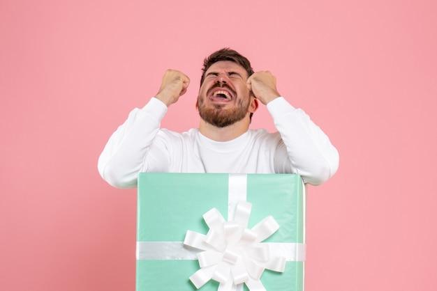 Vue de face du jeune homme à l'intérieur de la boîte actuelle en colère sur le mur rose
