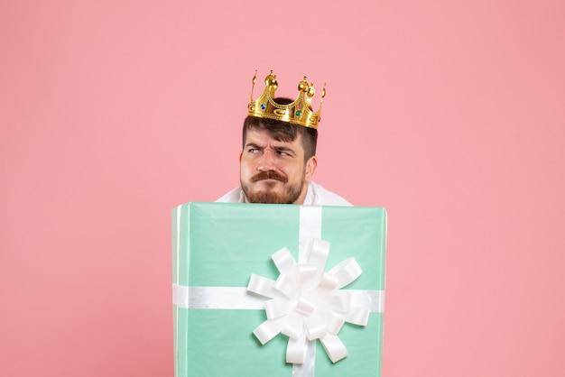 Vue de face du jeune homme à l'intérieur de la boîte actuelle avec couronne sur mur rose clair