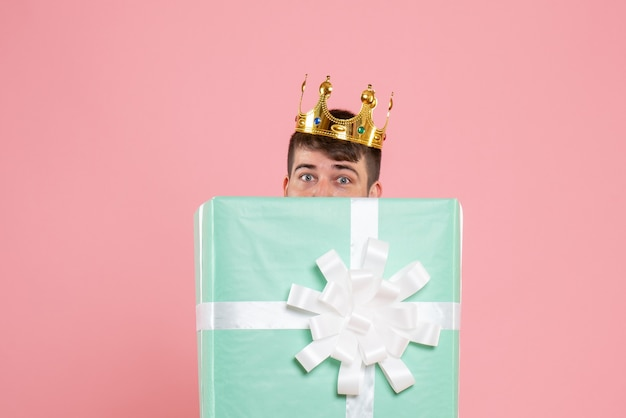 Vue de face du jeune homme à l'intérieur de la boîte actuelle avec couronne sur le mur rose