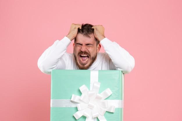 Vue de face du jeune homme à l'intérieur de la boîte actuelle hurlant sur le mur rose