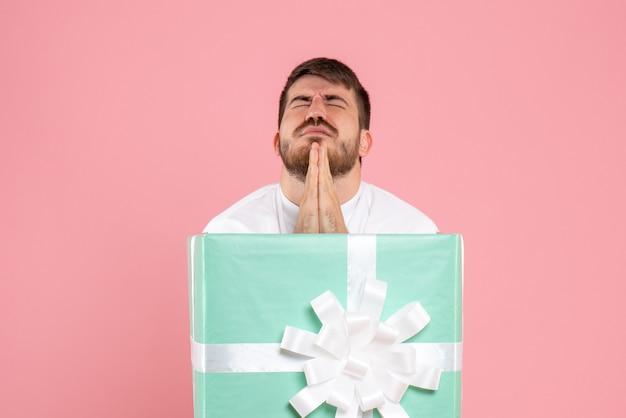 Vue de face du jeune homme à l'intérieur de la boîte présente priant sur un mur rose